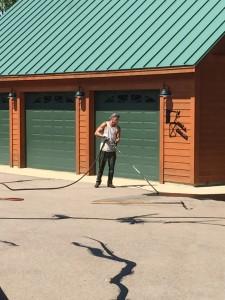 Worker sealing asphalt cracks with hot tar